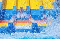 Мальчик с руками вверх наслаждается ездой на водных горках брызгая воду в парке aqua стоковое фото rf