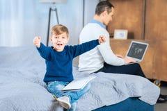 Мальчик с руками повышения книги чертежа в триумфе Стоковая Фотография