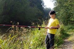 Мальчик с рыболовной удочкой стоковое фото rf