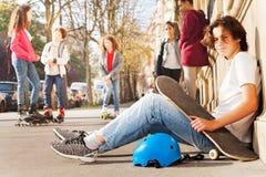 Мальчик с скейтбордом и шлем сидя на тротуаре Стоковые Изображения
