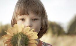 Мальчик с солнцецветом outdoors Игра детей в саде стоковые изображения rf