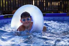 Мальчик с стеклами для плавать в бассейне плавает с раздувным кругом стоковые фото