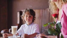 Мальчик с чашкой какао на кафе видеоматериал