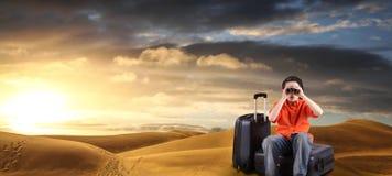 Мальчик с чемоданами и бинокулярное в пустыне Стоковая Фотография RF