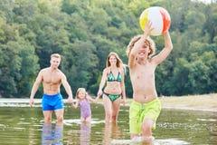 Мальчик с шариком играет весело в море стоковая фотография rf