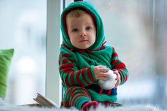 Мальчик с шариком сидит на предпосылке окна Стоковое Изображение