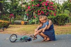 Мальчик упал с велосипеда, его затиров матери гипсолит на его колене стоковое изображение
