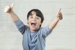 Мальчик усмехаясь показывающ большие пальцы руки вверх стоковая фотография