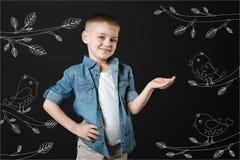 Мальчик усмехаясь пока птицы поя около его Стоковые Изображения