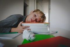 Мальчик утомлял усиленный чтения, делающ домашнюю работу стоковое фото rf