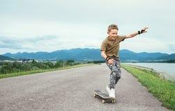Мальчик учит кататься на коньках на скейтборде стоковое изображение
