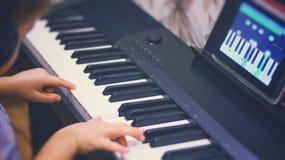 Мальчик учит сыграть рояль используя применение для цифровой таблетки Рояль клавиатуры Мальчик сидит на рояле и играет музыку на  Стоковое Фото