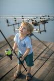 Мальчик учит уловить рыб в озере или реке стоковые изображения rf