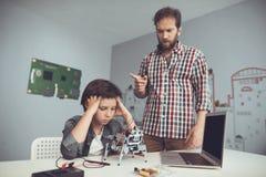 Мальчик ушиб робот Человек строго подвергает наказанию мальчик, объясняя к нему его ошибки Стоковые Изображения RF
