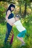 мальчик целуя его будет матерью супоросого живота Стоковая Фотография RF