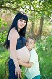 Мальчик целуя его будет матерью супоросого живота Стоковые Изображения RF