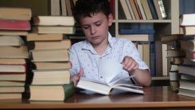 Мальчик читает толстую книгу и скучает по стеку книг видеоматериал