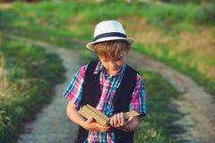 Мальчик читая книгу в поле Стоковая Фотография