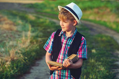 Мальчик читая книгу в поле Стоковые Изображения RF