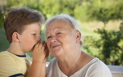 Мальчик шепча к бабушке в лете outdoors садовничает, внук стоковое изображение