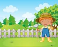 Мальчик держа сгребалку Стоковая Фотография