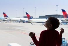 Мальчик Llittle смотря небо в авиапорте Стоковые Изображения