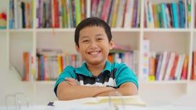 Мальчик Preteen сидя в библиотеке и усмехаться акции видеоматериалы