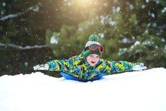 Мальчик sledding в потехе зимы снежного леса на открытом воздухе на каникулы рождества стоковые фотографии rf