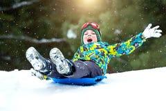 Мальчик sledding в потехе зимы снежного леса на открытом воздухе на каникулы рождества стоковые фото