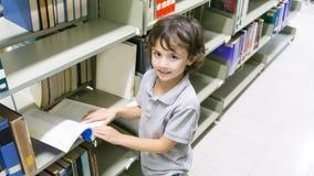 Мальчик Smiley белый с книгой и книжными полками на предпосылке стоковая фотография rf