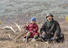 Мальчик Tsaatan, одетый в традиционном deel, с его дедом стоковые фото