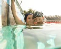 Мама давая сыну урок заплывания в бассейне во время стоковое изображение