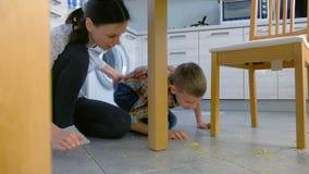 Мама бранит ее сына для разбросанной еды на поле кухни и делает его очистить вверх Чистые вверх хлопья мозоли с пола акции видеоматериалы