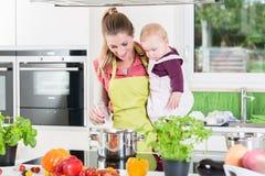 Мама варя с младенцем в руке Стоковое Изображение