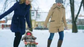 Мама вытягивает ее меньшего младенца на скелетоне в зиме видеоматериал