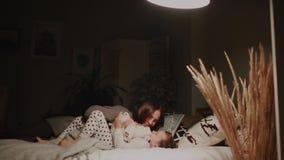Мама в спальне его дома пробуя положить для того чтобы положить маленького сына в постель сток-видео