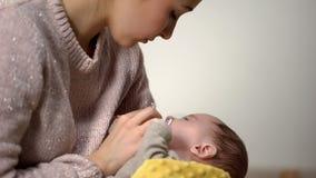 Мама давая меньшему прелестному ребенк ортодонтическое binky, аксессуары новорожденных ребят стоковые изображения