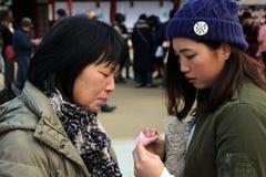 Мама & дочь проверяя результат удач-говорить бумагу стоковые изображения rf