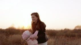 Мама играет при дочь, объезжая ее, оба смеясь над Съемка замедленного движения акции видеоматериалы