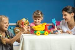 Мама играет с 2 дочерьми в добившийся успеха своими силами театре марионетки пальца стоковые изображения rf