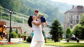 Мама играет с младенцем Мама целует и закручивает маленького сына в парке в медленном темпе видеоматериал