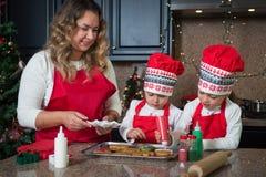 Мама и двойные девушки в красном цвете делая печенья рождества Стоковая Фотография