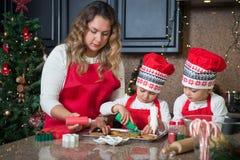 Мама и двойные девушки в красном цвете делая печенья рождества Стоковые Изображения