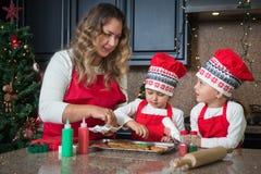 Мама и двойные девушки в красном цвете делая печенья рождества Стоковое Изображение RF