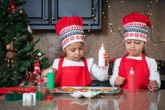 Мама и двойные девушки в красном цвете делая печенья рождества Стоковые Фото