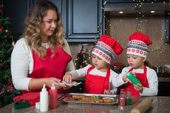 Мама и двойные девушки в красном цвете делая печенья рождества Стоковая Фотография RF