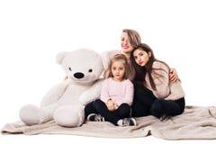 Мама и 2 дочери сидят на одеяле и объятии стоковое изображение