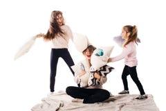 Мама и 2 дочери счастливо побили подушки и смех стоковое фото rf