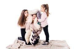 Мама и 2 дочери с подушками сидят и joyfully обнимают стоковое фото rf
