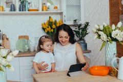 Мама и дочь в кухне стоковое фото rf